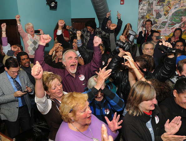Dan Vancoppenolle, center, cheers with his wife Sharon (left) as they celebrate Lawrence City Councilor Daniel Rivera's victory at El Taller restaurant. Rivera is claiming victory against Mayor William Lantigua. Photo by Carl Russo