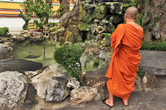 Reflective monk meditates at Chinese Pavilion, Wat Pho