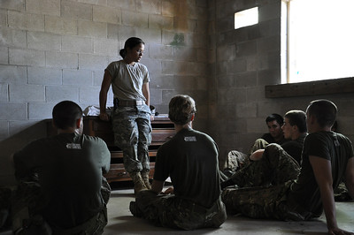 Mentorship - Former MLA Cadet and 2010 Instructor Sarah Hoover instructs her squad on MOUT operations (Military Operations in Urban Terrain) while training at the Fort Pickett MOUT Village.