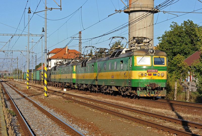 An iron ore train for the steel plant near Kosice runs through the station at Trebisov on the broad gauge line between the station building and the remainder of the standard gauge station! It is headed by ZS Cargo double electric locos 125-819/820 and 125-821/822 with another pair at the rear for this hilly section of the dedicated line.