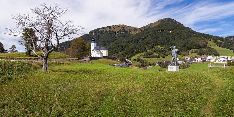 St. Nicholas Church (Župnijska cerkev sv.Nikolaja) and the Statue of the Slovenian impressionist Painter Ivan Grohar, in Spodnja Sorica