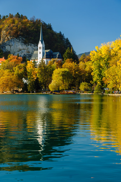 The St. Martin's Parish Church with fall foliage color reflected in the lake in Bled, Slovenia, Europe.