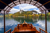 A tour boat framing Bled Castle reflected in Lake Bled, Slovenia, Europe.