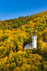 The Catholic Church of St. Mary with fall foliage color in the hills above Kropa, Slovenia, Europe.