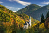 Fall foliage color and the Church of St. Mary of the Snows in the Kamnik Alps at Solcava, Slovenia, Europe.