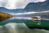 A tour boat  on a calm Lake Bohinj with fall foliage color, Slovenia, Europe.
