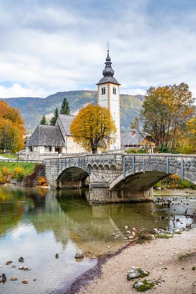 The Church of St John the Baptist reflected in Lake Bohinj, Slovenia, Europe.
