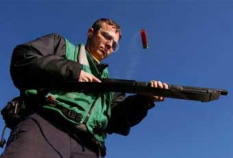 The 12 gauge shotgun is a manually operated (pump), repeating shotgun, with a seven-round tubular magazine, a modified choke barrel, ghost ring sights, and is equipped with a bayonet attachment, sling swivels and a standard length military stock with phenolic plastic buttplate (some models have wooden and/or folding stocks).