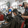 Bonao's Barber Shop was full of customers on Saturday, March 14, 2020. Owner Domingo Vicioso, pictured, said that he has only seen a tiny drop in business. They bought rubber gloves and hand sanitizer to help with the coronavirus. They are also cleaning much more then they did before. Vicioso has been in business for 11 years on Main Street in Fitchburg. Barber victor Vicioso, Domingo's cousin, cuts client A.J. Melendez's hair on Saturday in the packed shop. SENTINEL & ENTERPRISE/JOHN LOVE
