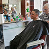 Bob Pelullo in his shop Ideal Barbers on Day Street in Fitchburg, March 14, 2020. He has been cutting hair at this shopo since 1961. His father opened it in 1948. He said that he is not that worried about the virus and this is the first time he has seen anything like this. He said that he has not lost any business due to the virus. It is mostly business as usual but he is not really sure how it will effect his business. This is the first time in all his years that he has seen any thing like this. He has bought more hand sanitizer. Veteran David Reyes got his hair cut on Saturday and said he was not to worried about the coronavirus. SENTINEL & ENTERPRISE/JOHN LOVE
