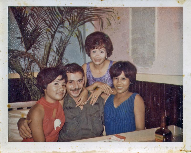 """Bill """"Speed"""" Palmer (NY) & 3 girls in Saigon -  Because Irving Carter (see next photo) had been wounded three times and was the only grunt in the field with 3 PHs, he was sent, along with Palmer, to an infantry company, Company C, 52nd Infantry which was attached to the 716th MP Battalion of the 18th MP Brigade.These guys were all grunts sent to Saigon for various reasons, and there is a series of fictional books based on the unit - the series is called Saigon Commandos.<br />     Here's what Palmer had to say about the duty: <br />     """"Guard duty consisted of 12 hours guarding the PX, enlisted and officer quarters, the motor pool, I even think we had to guard the dump. There were other places, Battalion HQ for instance. Being in the field was in some ways better. After the 12 hours of guard duty, we had to make formations (can you believe it?), square away our bunks, foot lockers, get haircuts, spit-shine our boots (crap like in Basic). I probably got more sleep in the field.<br />     """"It wasn't all that safe either. We were told to be wary of kids around the jeep; they would wrap rubber bands around the handle on a grenade, pull the pin and drop it in a gas tank (I don't know how they did that). When the rubber band dissolved in the gas...boom! The gooks would also throw grenades into the back of the open jeeps - boom. Also, everytime we pulled guard duty we were issued a different M-16. Now the one I had in the field was perfect for me; I zeroed in on the first three shots, and never missed what I was aiming at. If we left our quarters we were given a .45. (HA!)<br />     """"There was also the problem of determining who was an enemy. In the field, if they ran we shot them. Not so in Saigon. Also very weird to see a gook go over to the sidewalk curb, pull down his pants and take a shit - in the middle of the day with hoards of people going by. <br />     """"And, the rats were no smaller. Families living on stair landings in buildings with the rats running over and a"""