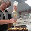 Karla Runge of Hinckley decorates chocolate chip cookie dough cupcakes Monday morning at Smallcakes in DeKalb.