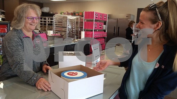 Kelly LePere (right) of DeKalb, admires a custom-made Chicago Cubs cake she picked up Monday morning at Smallcakes: A Cupcakery, 817 W. Lincoln Highway, Unit G, for her husband's birthday, before the shop's owner, Tina Wackerlin, rings her up. The shop features 17 signature cupcake flavors, dog treats, parfaits, gluten-free treats and more.