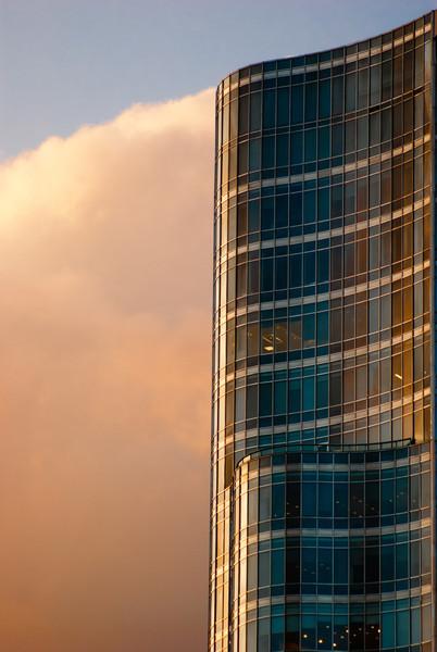 Prédio curvo e nuvem com luz do sol, São Paulo, SP