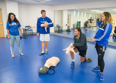 Students practice the response process for a choking infant in First Aid and Safety.