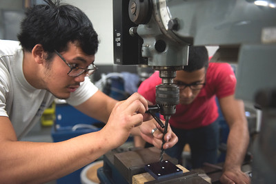 Theodore Pattarasnkol and Rohan Singh position a drill bit into their machine.