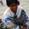 Today's smiling faces travel photo is of an ecstatic Bolivian boy who is taking joy in feeding a cluster of pigeons in La Paz, Bolivia.