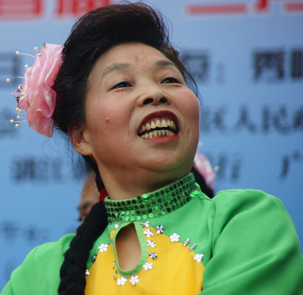 A Chinese lady Communist Performer flashes a big grin in Guilin, China as gleefully moves about on the stage in a public square.