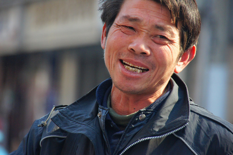 Today's smiling faces travel photo is of candid portrait of a Chinese man smiling on the streets of Shanghai, China with a big authentic grin on his face.