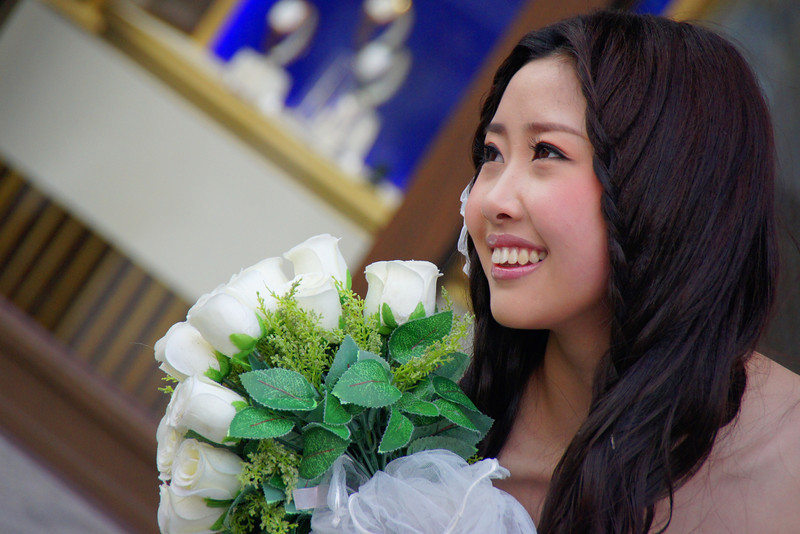 A lovely looking Chinese bride poses and smiles with a handful of flowers near the bustling Bund district of Shanghai, China.