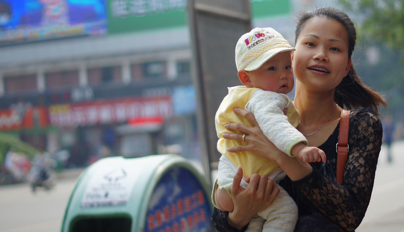 Today's smiling faces travel photo is of a Chinese mother carrying her baby while flashing a genuine smile in Yangshuo, China.