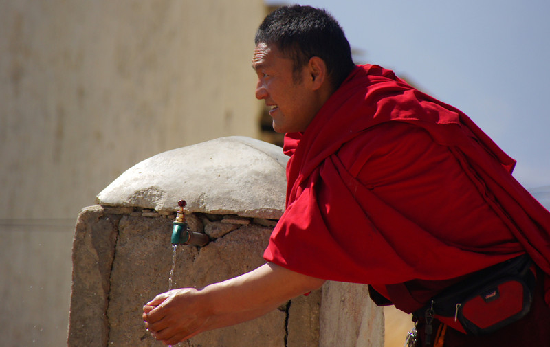 Today's smiling faces travel photo is of a Tibetan Buddhist monk grinning while he washes his hands in Zhongdian (Shangrila), China.