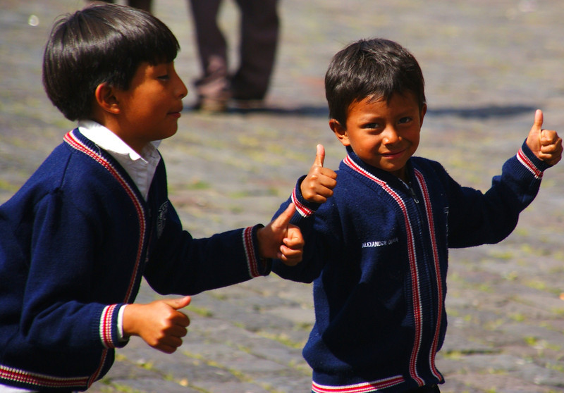Today's smiling faces travel photo is of a cute Ecuadorian boy moving about with his friend while smiling and giving the thumbs up - Quito, Ecuador.
