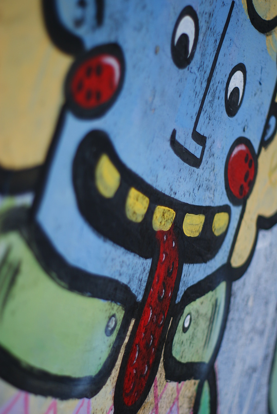 http://smilingfacestravelphotos.com : Today's daily smiling faces travel photo is of graffiti plastered on a wall in Quito, Ecuador. The face is smiling & sticking out its tongue.