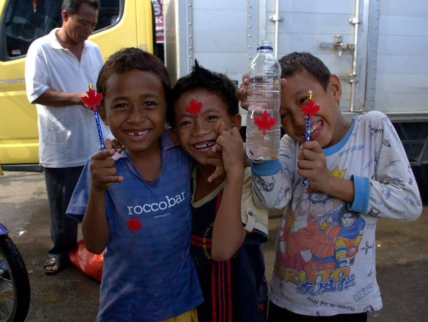 http://smilingfacestravelphotos.com : Cute Indonesian kids from Bintung showing off their newly acquired Canadian flags and pencils with a healthy does of smiles and grins.