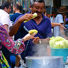 Today's smiling faces travel photo is of a Brazilian man smiling & smirking at one of his customers as he serves corn at the Ipanema Hippie Fair in Rio de Janeiro, Brasil.