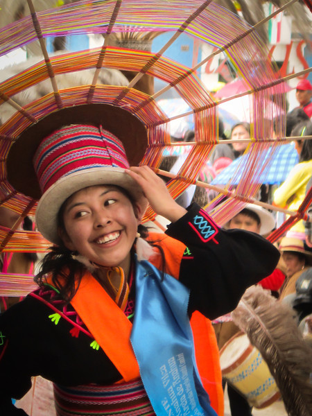 A smiling faces travel photo of a Peruvian lady wearing traditional attire at the Virgin de la Candelaria Celebrations taking place in  Puno, Peru.