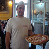 A smiling & friendly waiter serving up delicious pizza pies in Naples, Italy to delighted diners from all over the world.