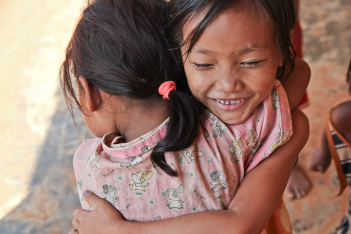 Today's daily smiling faces travel photo is of two adorable Khmer girls embracing one another for a cute huge while smiling.