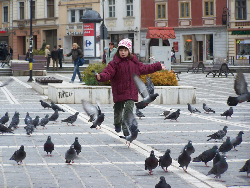 Today's smiling faces travel photo is of an excited young girl joyfully running through a flock of pigeons in Brasov, Romania.