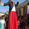 Today's smiling faces travel photo is of a street performer on stilts walking through the crowded market as he flashed a mischievous smile.