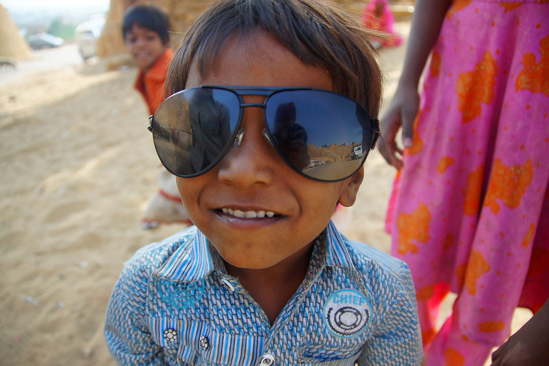 Today's feature smiling face photograph is of a cute boy trying on my over-sized men's sunglasses in the desert region of Jaisalmer, Rajasthan, India.