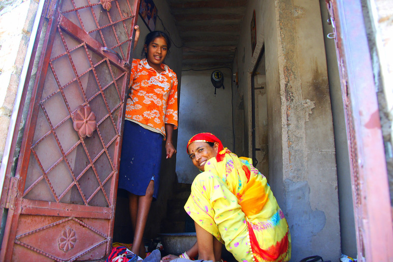 This is a travel photo of two Indian ladies kindly greeting me from the doorstep of their home as I wandered around the streets of Jodhpur, Rajasthan, India.