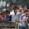 "<a href=""http://smilingfacestravelphotos.com"">http://smilingfacestravelphotos.com</a> : A travel photo of a group of teenagers riding on the back of a truck in Kolkata, India smiling, waving, laughing and posing for the camera."