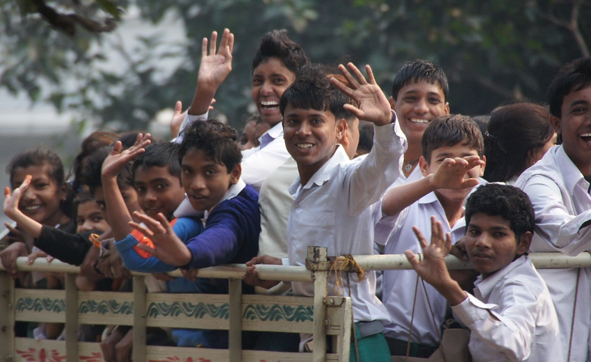 http://smilingfacestravelphotos.com : A travel photo of a group of teenagers riding on the back of a truck in Kolkata, India smiling, waving, laughing and posing for the camera.