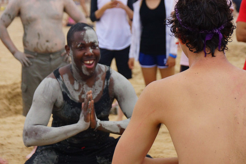 This is a travel photo of two foreigners smiling prior to engaging in a wrestling match at the Boryeong Mud Festival held at Daecheon Beach, South Korea.