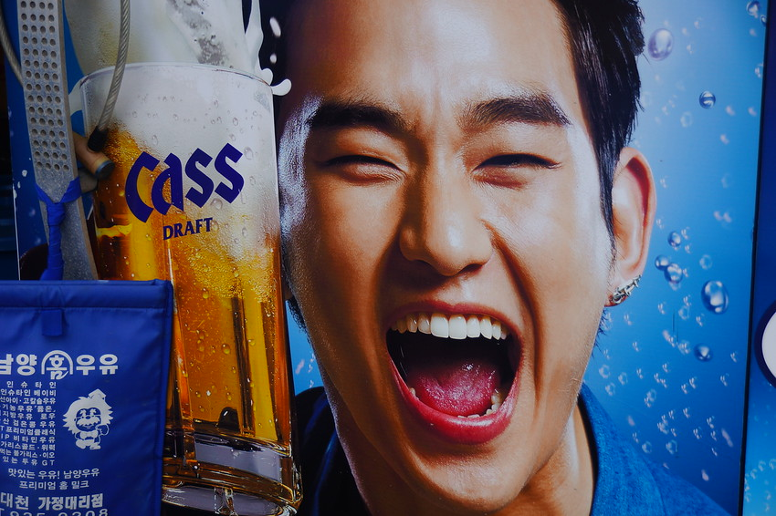 This is a daily smiling faces travel photo of a Korean man exuberant over drinking Cass Korean beer on this signboard I noticed in Seoul, South Korea.
