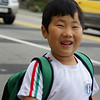Today's smiling faces travel photo is of a smiling Korean boy walking to school in the morning wearing a green backpack in Incheon, South Korea.
