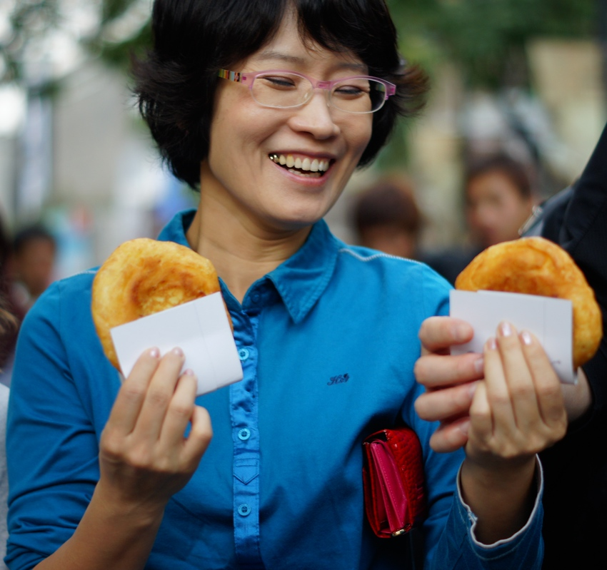 Today's smiling faces travel photo is of a Korean lady eating Hotteok (popular Korean pancake street food) in Insadong - Seoul, South Korea.