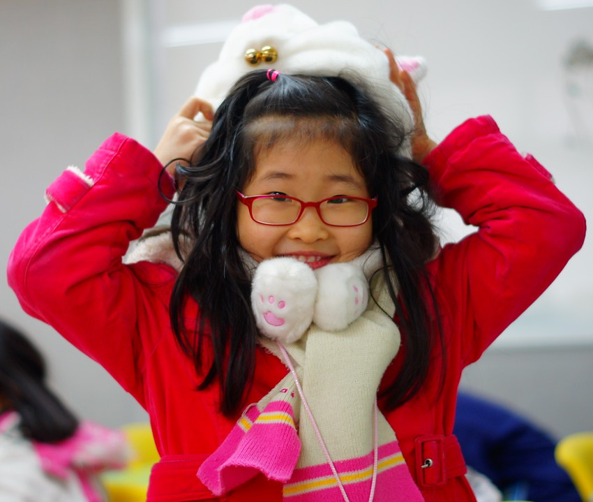 http://smilingfacestravelphotos.com : A cute Korean student wearing a warm winter hat, jacket and muffler smiles during a camp class break.