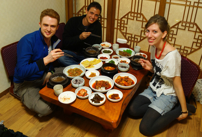 This is a group shot travel photo of some very hungry travel bloggers joyfully smiling and eagerly anticipating a delicious set Korean meal for lunch.
