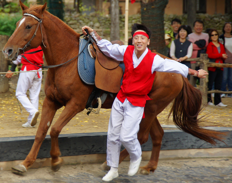 Today's daily smiling faces travel photo is of a Korean equestrian performer doing stunts and tricks with a horse riding around a circle ring at the Korean Folk Village - Yongin, South Korea.