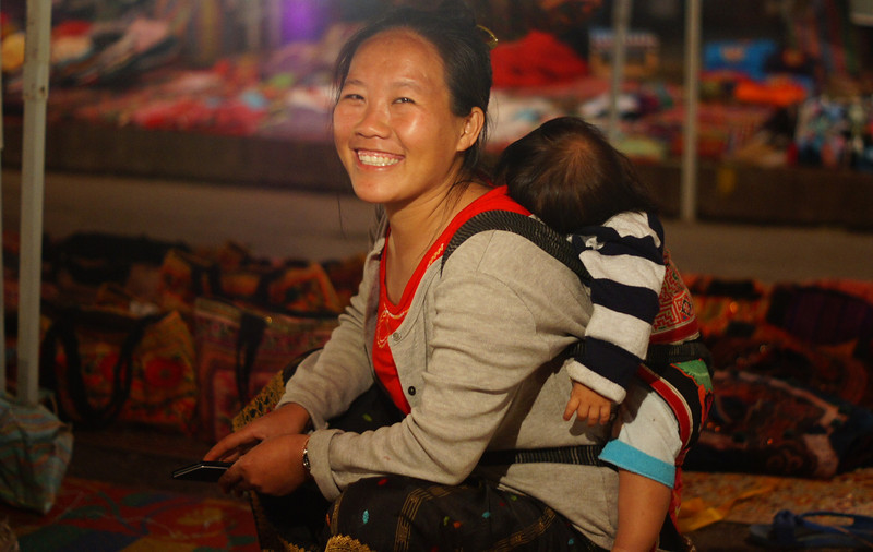Today's Smiling Faces Travel Photo is of a lovely Lao lady smiling while carrying her baby on her back at the tourist night market in Luang Prabang, Laos.