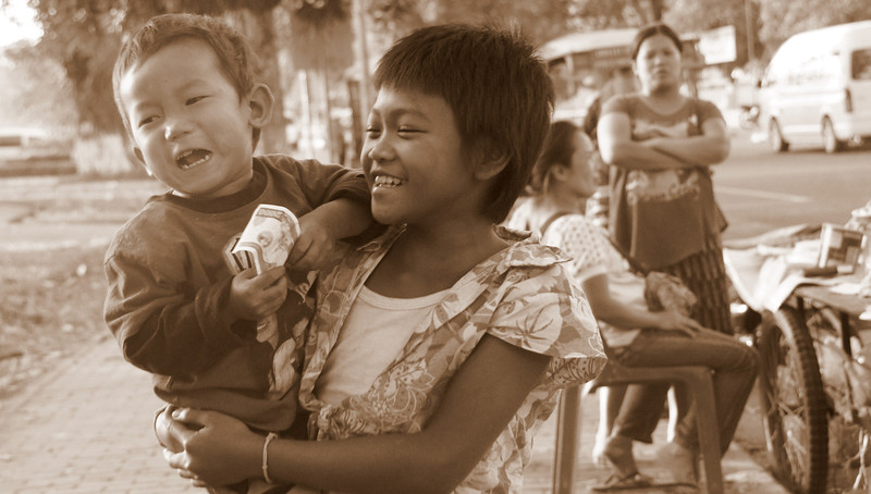 Today's smiling faces travel photo is of a lovely grinning girl holding her cute brother nearby the Mekong River in the capital city of Vientiane, Laos.