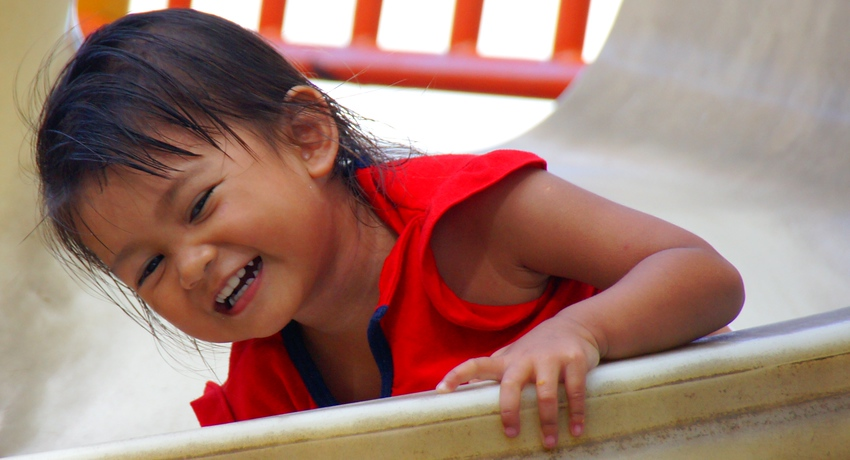 Today's smiling faces travel photo is of an adorable Malaysian child smiling as she plays on a slide in GeorgeTown, Penang, Malaysia.