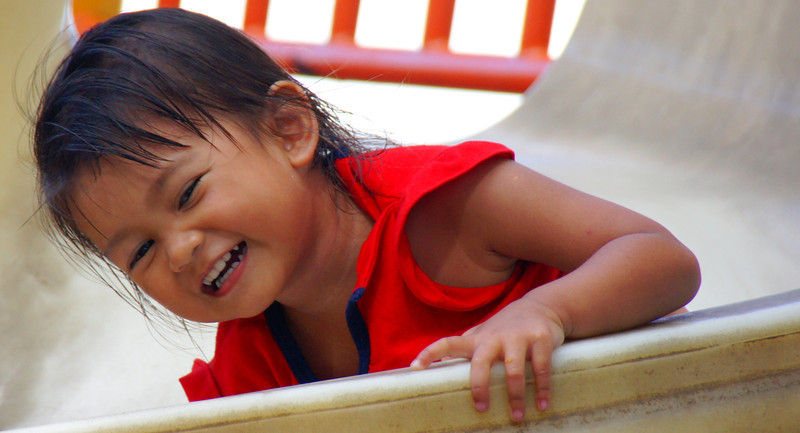 """Today's smiling faces travel photo is of an adorable Malaysian child smiling as she plays on a slide in GeorgeTown, Penang, Malaysia:<br /> <a href=""""http://www.smilingfacestravelphotos.com/travel-photos/child-playing-penang-malaysia"""">http://www.smilingfacestravelphotos.com/travel-photos/child-playing-penang-malaysia</a>"""